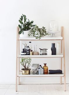 shelf in the bathroom that holds useful and beautiful jars and vases.