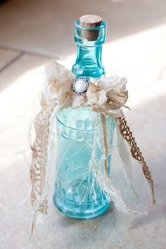 An easy DIY wedding decoration is a coloured or plain glass bottle finished off with a pretty lace and silk ribbon bow. You can buy lengths of ribbon and lace trimmings in most fabric shops. You could even add beads to create a different kind of look.