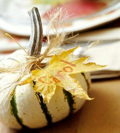 Pumpkin Place Cards - Using a metallic marker, write names on various leaves and tie them to the pumpkin stems with short pieces of twine