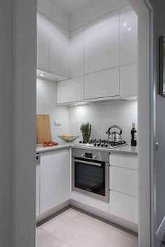 Petite cuisine. Différence d'hauteur des meubles hauts pour délimiter les postes de travaux. Meuble blanc brillant. Les meubles montant jusqu'au plafond apporte de la hauteur.