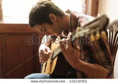 Practicing in playing guitar. Handsome young men playing guitar - stock photo