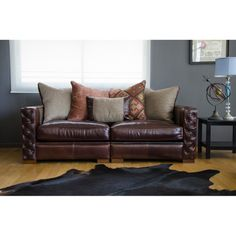 This leather sofa features beautiful button detailing, luxurious character leather and an eclectic fabric arrangement. Outfitted around a premium kiln-dried hardwood frame, this sofa gives maximum comfort and relaxation.