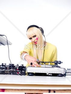 portrait image of a young woman wearing headphones with dj mixture in foreground. - Close-up shot of DJ mixture with young woman wearing headphone against plain white background.