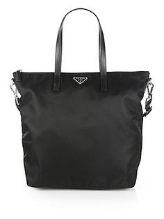 """Prada Vela Zip Top Tote $790 Lightweight nylon in a timeless design accented with luxurious saffiano leather trim and an iconic logo emblem. Double saffiano leather top handles, 8"""" drop Detachable adjustable shoulder strap, 12""""-21"""" drop Top zip closure Protective metal feet One inside zip pocket Two inside open pockets Logo lining 13""""W X 14""""H X 6""""D Nylon/leather Made in Italy"""