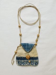 A beautiful patchwork talisman pouch, made using hand woven, indigo dyed hemp, indian cotton and natural linen. It has hand stitched details around the edge and the button and beads are made from bamboo and wood. A small flap holds everything in place. These talisman pouches are normally worn around the neck to carry small precious keepsakes. Slowly and carefully handcrafted using all natural materials :) Approximate size of the pouch is 95mm high, by 100mm wide.  Ref: BTP107