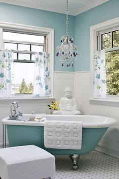 A little bling (the chandelier) and a little zen (the Buddah) in this airy corner bathroom.