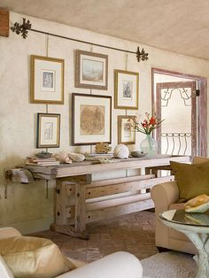 Gather Antiques:   Combine a variety of pieces to create a cohesive look. Here, a 19th-century carpenter's workbench stands in as a console table. The raw, unfinished wood fits perfectly in the rustic space. Artwork hung from S hooks and chains on a wrought-iron curtain rod forms a unique gallery. Give the gallery arrangement a cohesive look by choosing one shape for all the frames.