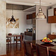 """a sala de jantar para acomodar mais convidados sentados, mas sem abrir mão da privacidade da copa no dia a dia. A solução foi substituir a parede pela porta de correr. """"Com duas folhas de MDF de 1,20 m de largura cada uma, ela tem pintura gofrato cinza (cor S168, da Sayerlack), que dá acabamento fosco e é mais fácil de limpar"""", diz o arquiteto Luciano Dalla Marta, do LDM Arquitetura. Quando as folhas estão abertas, é possível juntar as mesas que são do mesmo modelo, assim como os lustres."""