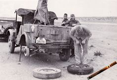 A Afrika Korps Kfz 4 getting a flat tire repaired while operating in North Africa