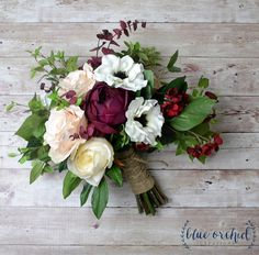 Fall wedding bouquet of silk flowers and artificial greenery. This bridal bouquet has a boho, hand-tied- shape and is full of beautiful colors and textures. Silk flowers and greenery are mixed together to create a stunning, statement bouquet. Burgundy cabbage roses, peonies,