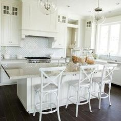 Staggered white cabinets over arabesque backsplash and gas range