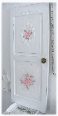 Repurposed door. The embossed areas can be achieved by carefully applying texture paste through a stencil using a painting knife (tape the stencil to the door), then when it's dry; paint over it. Resin mouldings would also work.