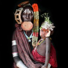 Surma people, Ethiopia. - Body paintings are used to extol beauty and attract the opposite sex. The large disks that Surma women use as earrings and lip ornaments are made from baked clay colored with ochre and is used for aesthetic and economic reasons.