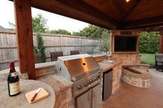Outdoor kitchen with stainless BBQ, sink, and refrigerator. Natural stone countertops. By Outdoor Signature in Argyle, TX