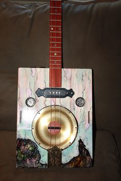 This guitar was hand made and hand painted. The Guitar has a single coil pick up, oak neck, Mandolin tail piece, abalone dots, 2 sound holes, is 3 string, has a resonator, volume and tone controls, exotic wood bridge and open gear tuners. The body was built by me, and my wife