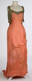 1906 Year  to:1910 Description:A pseudo-tunic-style pink color-colored silk brocade satin of a large chrysanthemum-like pattern; the front panel is caught up and looped to the right side; a back train falls to form into a point with a pink cording and 2 weights; back underarms looped at waist to fall into 2 tail-like trains, underarms have a metallic silver lace with white chiffon and white satin lining; back of gown falls in a low V-shape; heavy beaded trim of gold, silver and pearl beads…