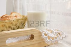 Glass of milk and a basket of bread on the background of a window Stock Photo