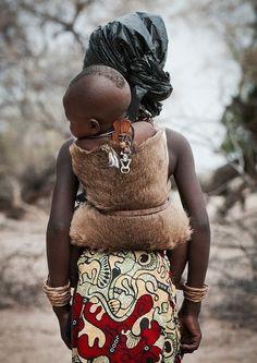 """mysumb: """" Mukubal Girl Carrying Her Brother in a Dik Dik skin, Angola by Eric Lafforgue """""""