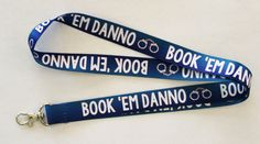 """Book 'Em Danno"" Lanyard Inspired by Hawaii Five-0 Show everyone at work who's really boss with this awesome lanyard! Features: - Lobster Clasp Closure - 17.5"" Long High Quality Lanyard Ribbon Materia"