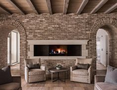 Gorgeous cottage living room boasts a stunning plank ceiling accented with wood beams and gray brick framing arched doorways and a long narrow fireplace fixed to the wall behind gray Greek key chairs topped with gray pillows and placed flanking a round wood and metal coffee table.