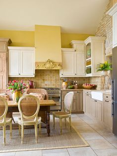 Cabinets with differing heights and finishes suggest the kitchen evolved over time, which is what drew the homeowners to the country French style. By scouring antiques shops and thrift stores, the homeowners collected old doors, shutters, and the plaster piece that now takes center stage on the range hood.