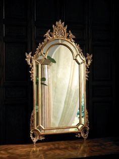 Baroque mirror with mirrored borders finished in antique gold metal leaf.