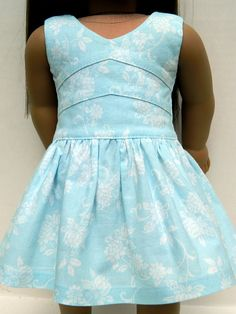 Delicate light blue and white floral print cotton dress features a beautifully detailed, fully line bodice and a full skirt that is slightly longer in