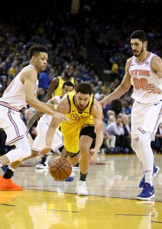 23ece8cdf43 Klay Thompson of the Golden State Warriors tries to dribble between Kevin  Knox and Enes Kanter