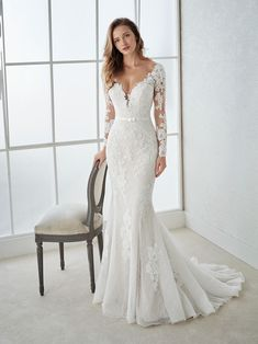 Sensual wedding dress with illusion neckline and long sleeves with a second-skin effect. An elegant low waist mermaid design, with a V-neck, which streamlines the silhouette and accentuates feminine curves. A dress made of embroidered tulle, lace and grosgrain complemented with a delicate waistband.