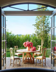 a view of four chairs around a table with flowers Jessica Alba, Architectural Digest, Greenwich Village, Hollywood Hills, Ellen Degeneres And Portia, Side Deck, Los Angeles Homes, Outdoor Furniture Sets, Outdoor Decor
