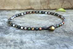 This anklet made with 4mm fancy jasper semiprecious stone beads woven together with dark brown wax cord and brass bell for closure. * Length is approx