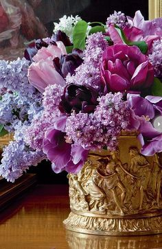 Lilac and tulips in lavender tones fill this gold detailed container.