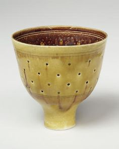 Tall footed bowl, pierced, porcelain, natural uranium yellow glaze over exterior and recessed foot, three pairs of manganese rings, one pair encircling interior foot.  Decoration The central section is pierced with holes which the glaze has filled and the interior is manganese with two pairs of finely incised bands