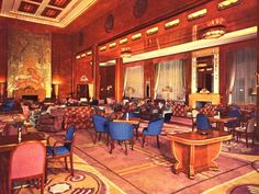 The Queen Mary ~ This is a view of the first class Lounge in the 1950s with its posh armchairs, settees and burled wood tables, all since replaced with convention furnishings.  The unicorn mural above the marble fireplace concealed a movie projector that gave the room a dual function as a cinema.