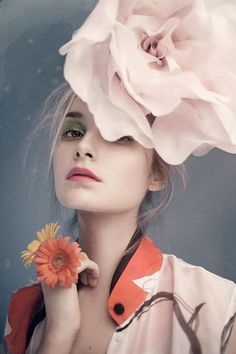 beautiful young woman with a flower hat and flower rings, fashion editorial