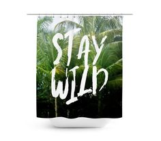 """Even if you can't make it to the beach today, why not add a piece of it  your vanity bathroom settings with this vibrantly stylish shower curtain  accent, featuring a lush backdrop of tropical green palm trees throughout!  Measuring at 71x74 inches with a twelve buttonhole eyelet rim for ease of  hanging, and adorned with the words """"Stay Wild"""" from end to end, hang out  in nature when you relax behind the allure of this inviting surf tropical  setting!   *Available in 71x74 inc..."""