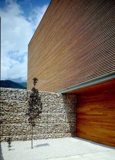 Gabion wall and wood slats house                                                                                                                                                                                 More