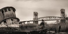 An old wooden tugboat weathers along the Cape Fear River in Wilmington NC with the Memorial Bridge in the background.