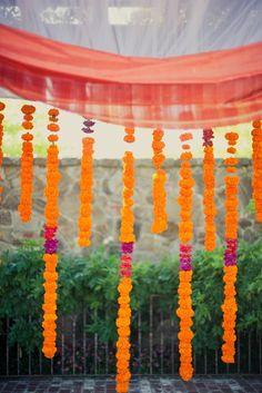Strings of orange and purple marigold flowers in outdoor Indian wedding mandap via IndianWeddingSite.com