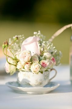 Beautiful petite soft pink roses w/baby's breath tucked into a floral porcelain tea cup w/saucer...