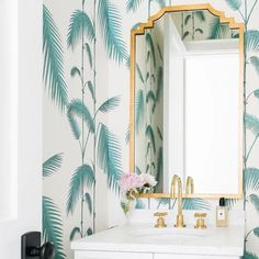 Cole & Son Palm Leaves Wallpaper displays an ivory and blue palm leaf pattern in a bathroom accented with a gold leaf art deco mirror. Wallpaper Display, Art Deco Wallpaper, Art Deco Spiegel, Blue Powder Rooms, Palm Leaf Wallpaper, Bathroom Wallpaper Tropical, Bathroom Accents, Art Deco Mirror, White Vanity