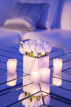 A reflective surface emphasizes the brilliance of white votives and tulips.