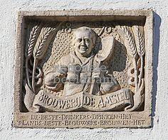 Een gevelsteen met de slagzin van brouwerij De Amstel en een afbeelding van een brouwer met een bierpul in een hand en een schep in de andere