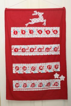 This design is on a red linen background. The pockets and appliqued reindeer are on a polycotton mix with a design of blue and red reindeer and snowflakes. The numbers and felt circles are all hand embroidered into place. Dimensions - 64 x 92 cms, hanging length is 105 cms. Pocket dimensions are 8 x 10 cms Price - £35