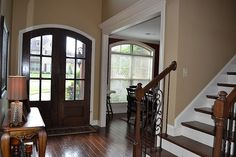 Beautiful front doors and staircase railing in this warm foyer.  #entryways  #foyers  homechanneltv.com