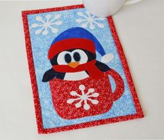 SAVE FOR LATER Cute unique mug rug for Winter. Great Gift idea.  Easy quilted pattern Lisa_Marie.'s Pattern Store on Craftsy  Cup O'Winter (Penguin) Mug Rug Pattern