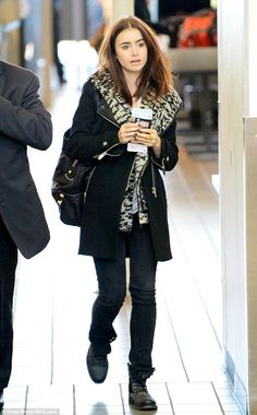Jet-setter: Lily Collins tried to make a low-key departure out of LAX on Monday and didn't seem too thrilled by all the attention her presence incited