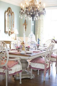 white dining table & chairs; red & white chair cushions; blue walls; gold detailing