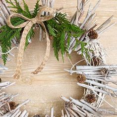 Broken twigs gathered from the yard adorn a grapevine wreath. White spray paint unites the twigs and gives the wreath a snow-dusted outlook; tiny pinecones, a jute-ribbon bow, and fresh greenery underscore the wreath's woodland premise./