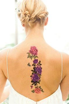 Watercolor floral back piece along the spinal column.